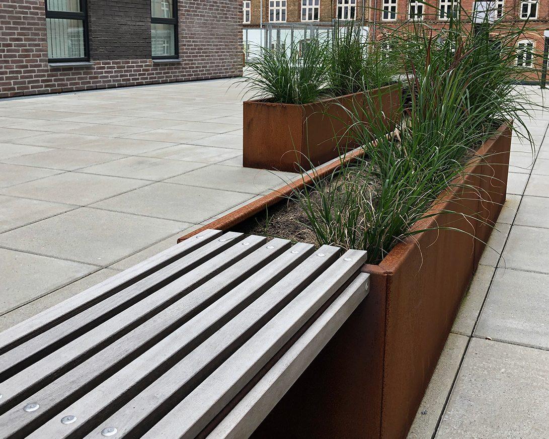 De enkle linjer i Land Modern designet fra danske Land Højbede passer fint til det moderne byggeri mens planterne bløder op