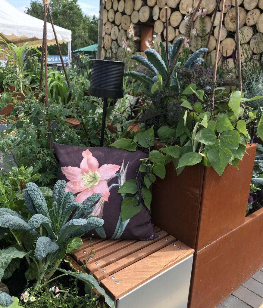 Billedet viser et lille hjørne af inspirationshaven Det rummelige haverum ved CPH Garden 2019. I plantekummerne ses en blanding af blomster, urter og grøntsager.