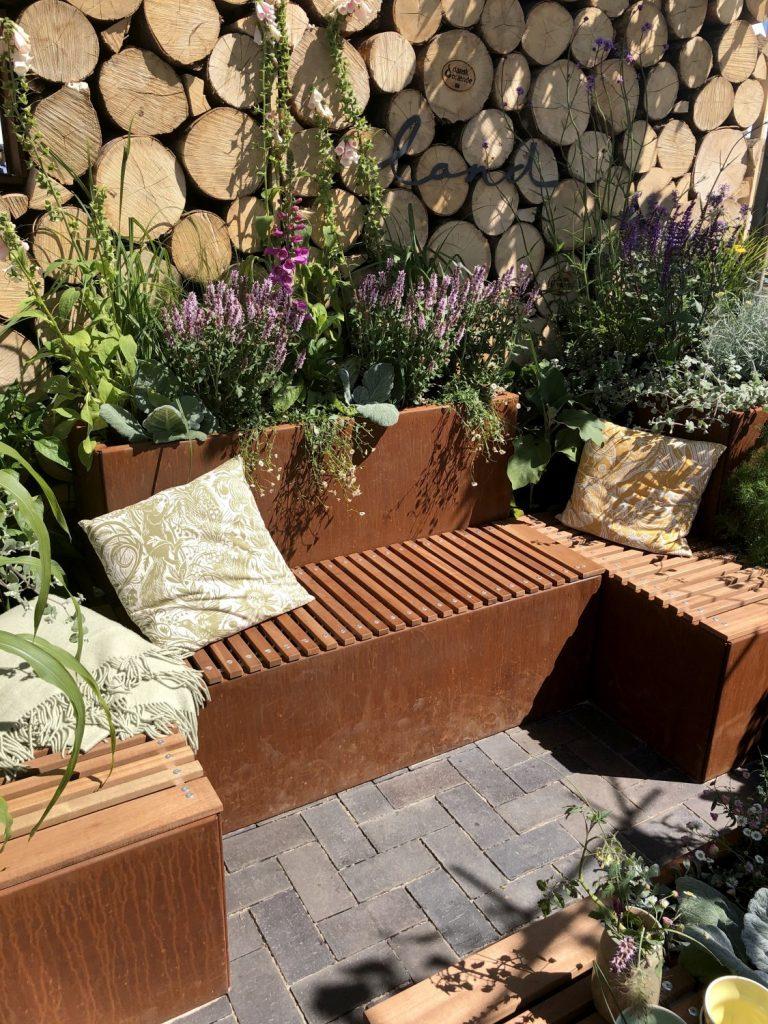 viser en fin hyggekrog bygget op af plantekummer med siddepladser i mahogni, fra Land Højbede