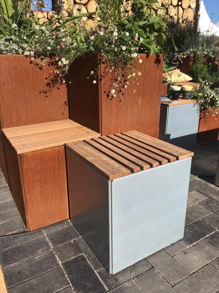 viser Land Modern plantekummer i corten og højgalvaniseret magnelis stål med sæder i mahogni fra Land Højbede