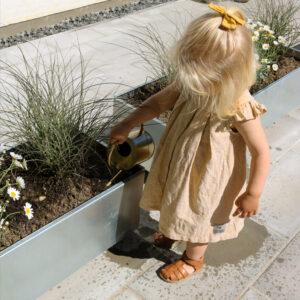 Land Classic højbed 40x120 cm galvaniseret med græsser og sommerblomster på terrassen hos Line B. Andersen sommer 2020, sød lille pige vander