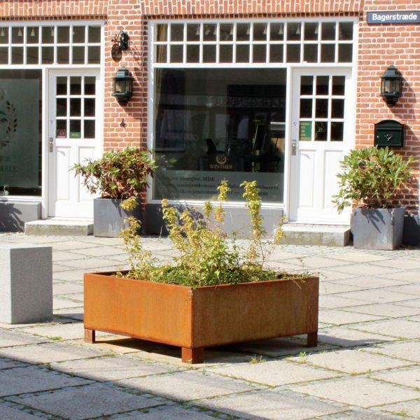 Land Modern 120x120cm kvadratisk plantekumme med ben i Corten på torv i Fredensborg