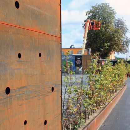 Forlænget plantekumme fra Land Højbede brugt som skillerum mellem vej og torv