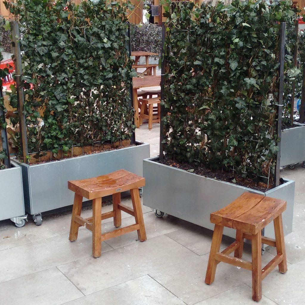 Plantekummer med hjul fra Land Højbede brugt som mobil afskærmning